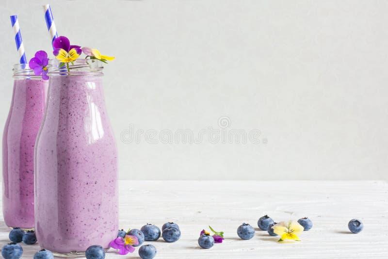Bosbes smoothie of milkshake in flessen met bloemen en stro royalty-vrije stock fotografie