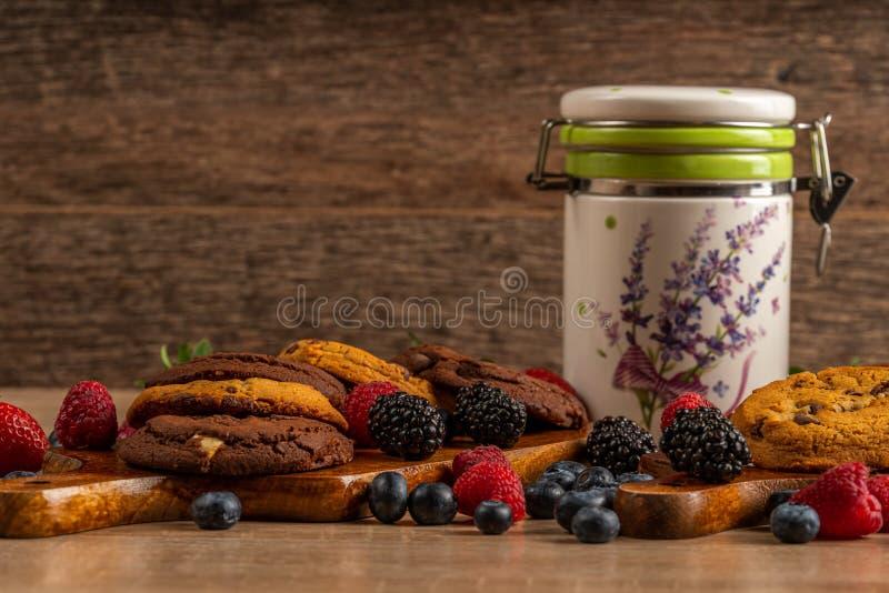 Bosbessen, braambessen, aardbeien, chocoladekoekjes en ceramische kruik op houten lijst met exemplaarruimte stock afbeeldingen
