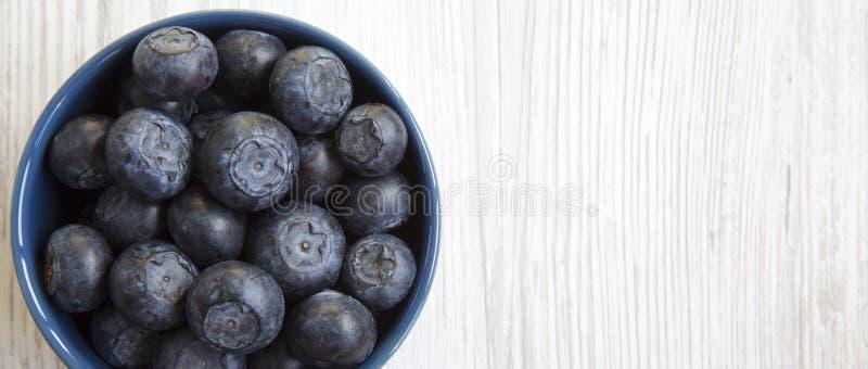 Bosbessen in een blauwe kom, luchtmening Organische superfood Ruimte voor tekst stock afbeeldingen