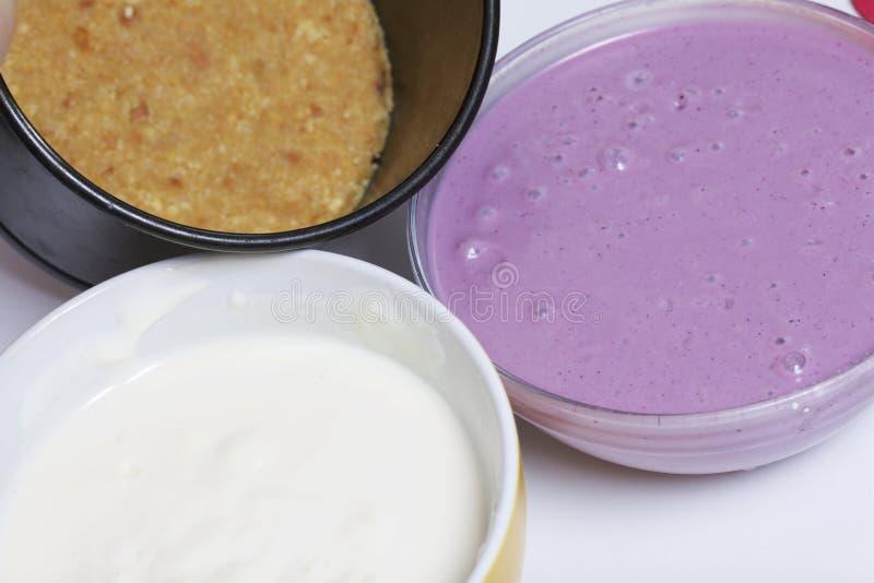 Bosbessenkaastaart Koekjesbasis, gestremde melkgelei met zure room en bosbessenjam De ingrediënten voor het koken worden gevestig stock foto's