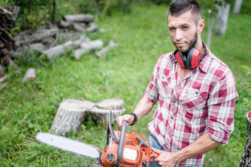 Boscaiolo maschio con il legno ed il legname di taglio della motosega fotografia stock