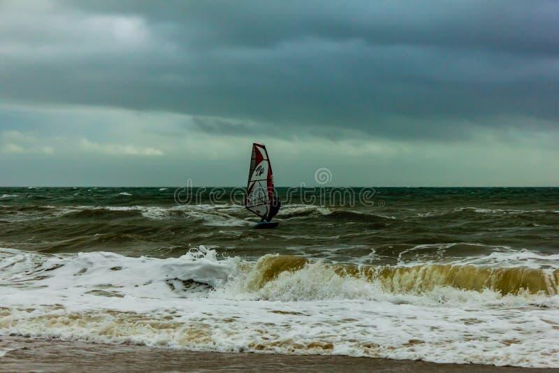 Boscombe, Dorset/het Verenigd Koninkrijk - Januari 26, 2019: Windsurfer in een ruw water en een donkere hemel stock afbeeldingen