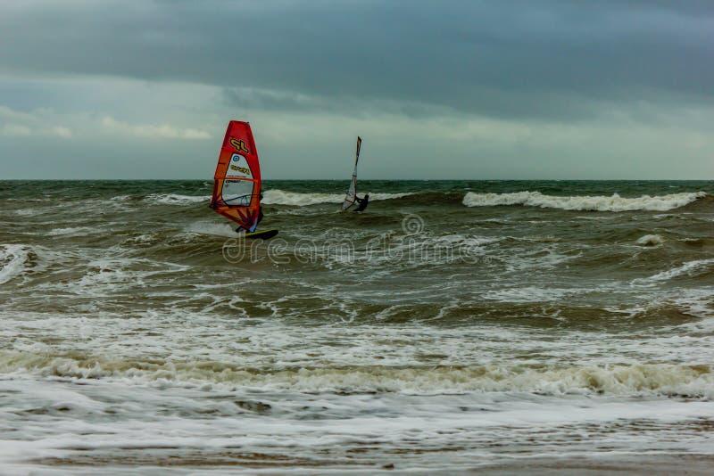 Boscombe, Dorset/het Verenigd Koninkrijk - Januari 26, 2019: Windsurfer in een ruw water en een donkere hemel royalty-vrije stock foto