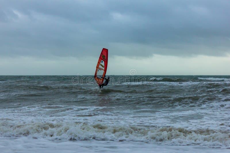 Boscombe, Dorset/het Verenigd Koninkrijk - Januari 26, 2019: Windsurfer in een ruw water en een donkere hemel royalty-vrije stock fotografie