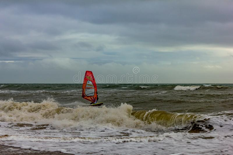 Boscombe, Dorset/Regno Unito - 26 gennaio 2019: Windsurfer in un mare in tempesta ed in un cielo scuro fotografia stock libera da diritti