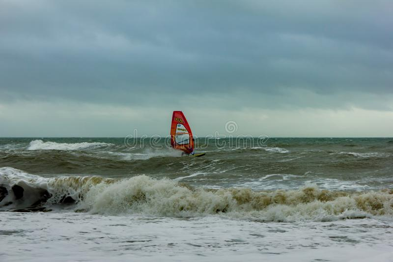 Boscombe, Dorset / United Kingdom - January 26, 2019:  Windsurfer in a rough water and dark sky.  stock images