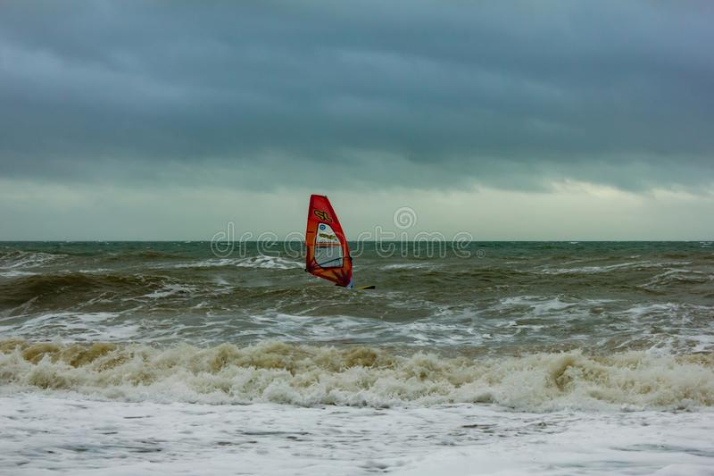 Boscombe, Dorset / United Kingdom - January 26, 2019:  Windsurfer in a rough water and dark sky.  stock image