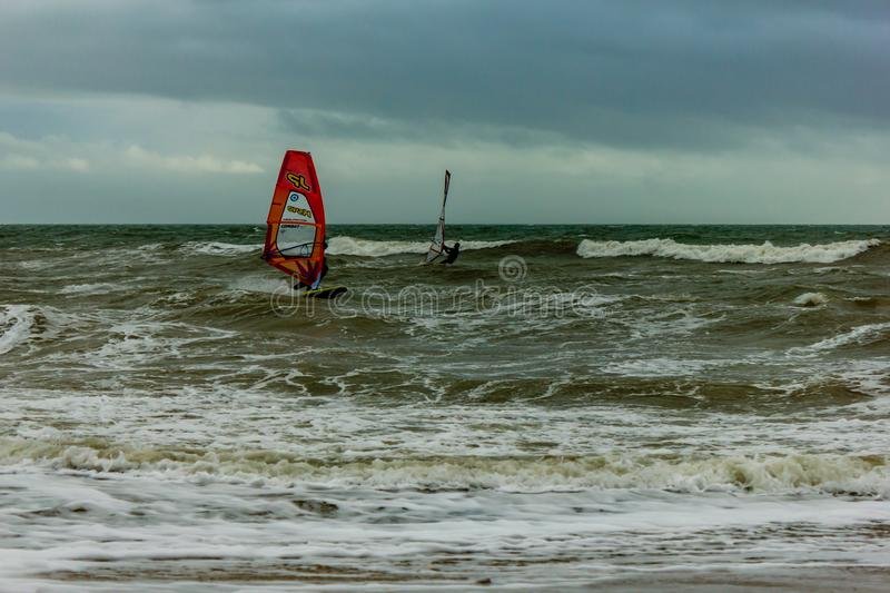 Boscombe, Dorset / United Kingdom - January 26, 2019:  Windsurfer in a rough water and dark sky.  royalty free stock photo