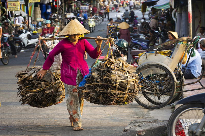 Bosego wietnamczyka dojrzała kobieta w conical Azjatyckim kapeluszowym przewożenia drewnie w ruchliwej ulicie na Luty 13, 2012 w  zdjęcia royalty free