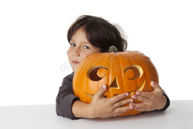 Boshafter kleiner Junge mit einem Halloween-Kürbis stockfoto