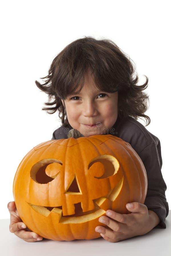 Boshafter kleiner Junge mit einem Halloween-Kürbis stockbilder