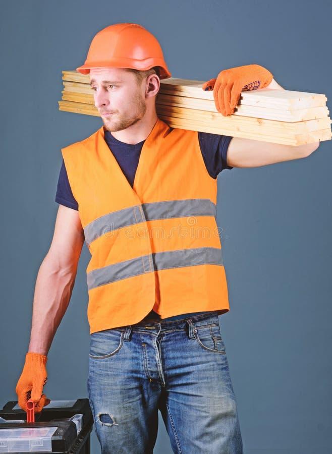 Boskennisconcept De timmerman, schrijnwerker, arbeider, bouwer op bezig gezicht draagt houten stralen op schouder Mens, manusje v royalty-vrije stock foto