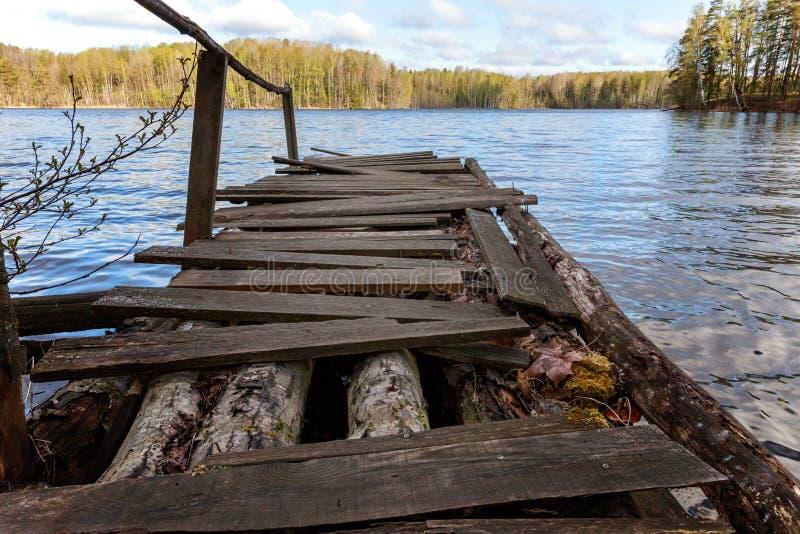 Bosmeer of rivier op de zomerdag en oude rustieke houten dok of pijler royalty-vrije stock afbeeldingen