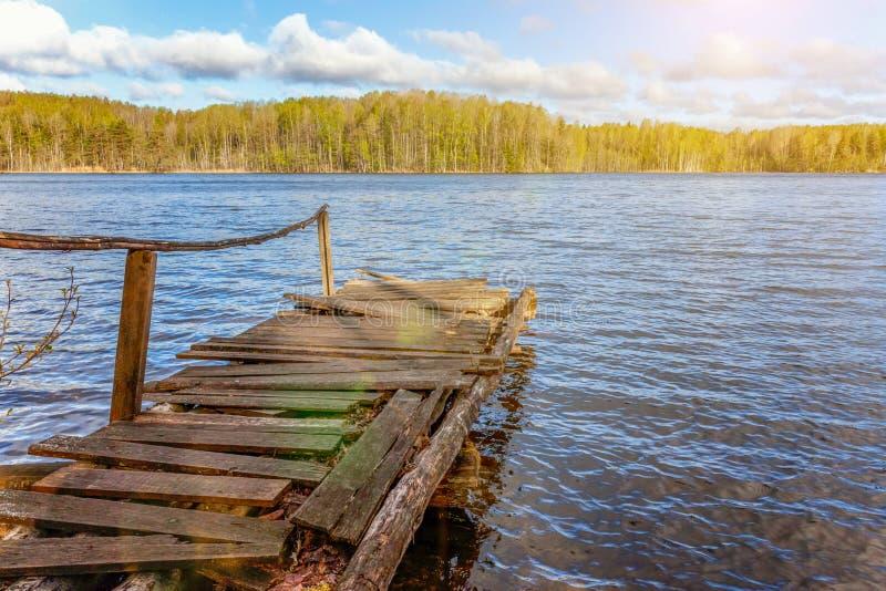 Bosmeer of rivier op de zomerdag en oude rustieke houten dok of pijler royalty-vrije stock afbeelding