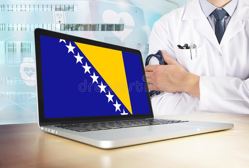 Bosnia Herzegovina healthcare system in tech theme. Bosnian flag on computer screen. Doctor standing with stethoscope in hospital. Cryptocurrency and stock photography