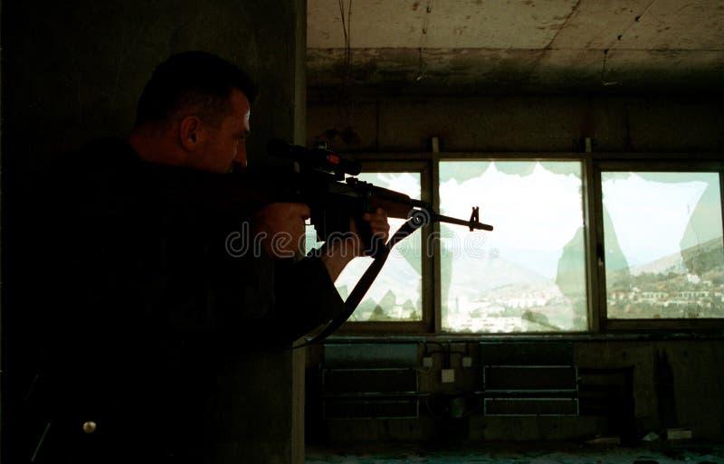 BOSNIAN CIVIL WAR. MOSTAR, BOSNIA, 17 AUGUST 1993 - A Bosnian Croat sniper takes careful aim at a group of Bosnian Muslim civilians shopping at an outdoor market stock photo