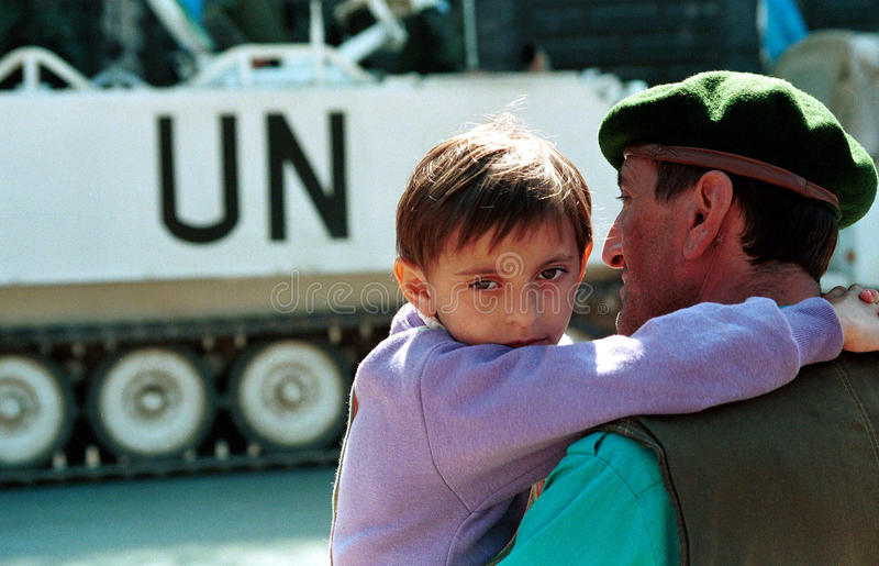 BOSNIAN CIVIL WAR. SARAJEVO, BOSNIA, 19 JULY 1994 --- A Bosnian boy and his father watch United Nations troop carriers drive through the besieged city. (C) Photo royalty free stock image
