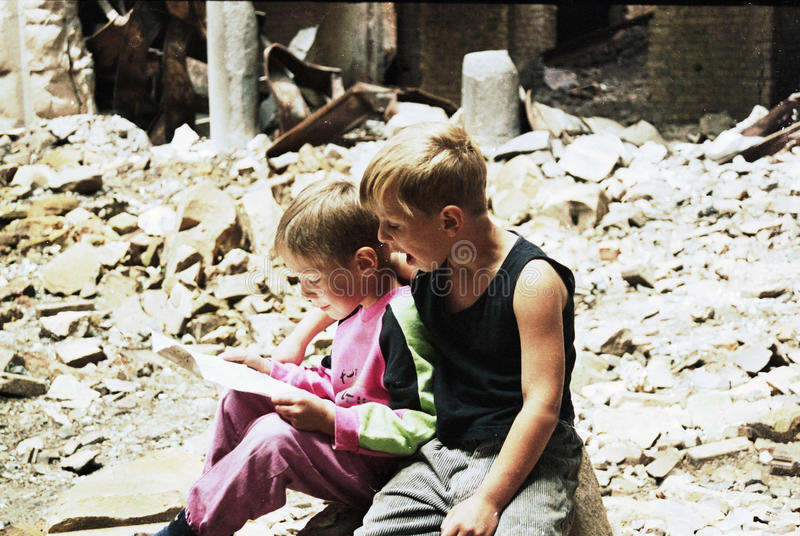 BOSNIAN CIVIL WAR. Two young boys read a page from a book in the recently destroyed National and University Library of Bosnia in Sarajevo, Bosnia, on Monday stock photography