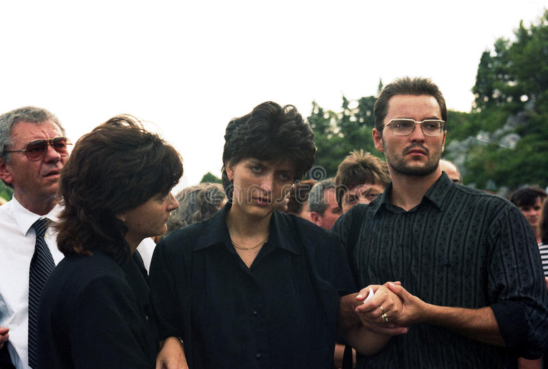BOSNIAN CIVIL WAR. A woman in comforted by her family after the funeral for her fallen soldier husband in Gornji Vakuf, Bosnia, on Tuesday, August 17, 1993 stock image