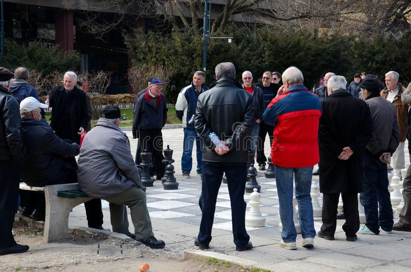 Bosnian men play chess on giant board in public square Sarajevo Bosnia. Sarajevo, Bosnia - March 23, 2015: A group of Bosnian men entertain themselves by stock photos