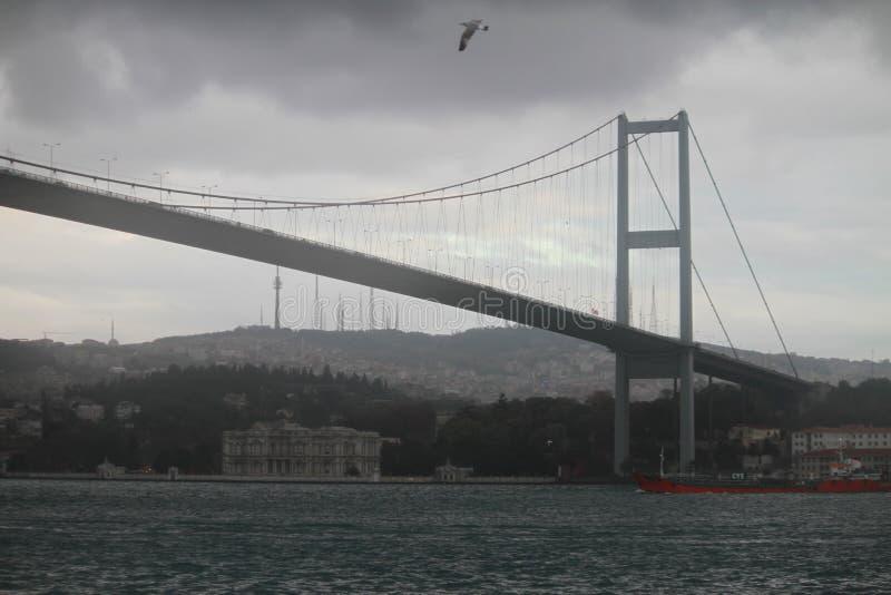Bosphorous bro och ett rött skepp i Istanbul, Turkiet royaltyfri fotografi