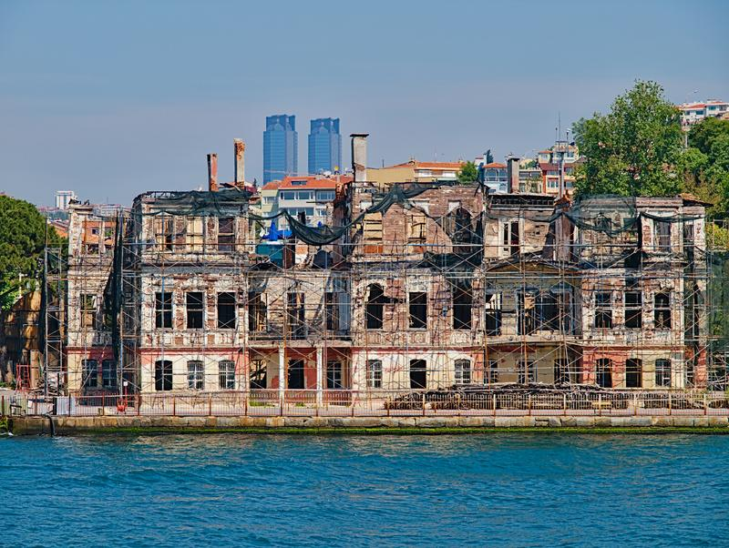 Bosporus strait, view from cruise ship. Old traditional damaged wooden building with structural support and TAT twin towers at the stock photos