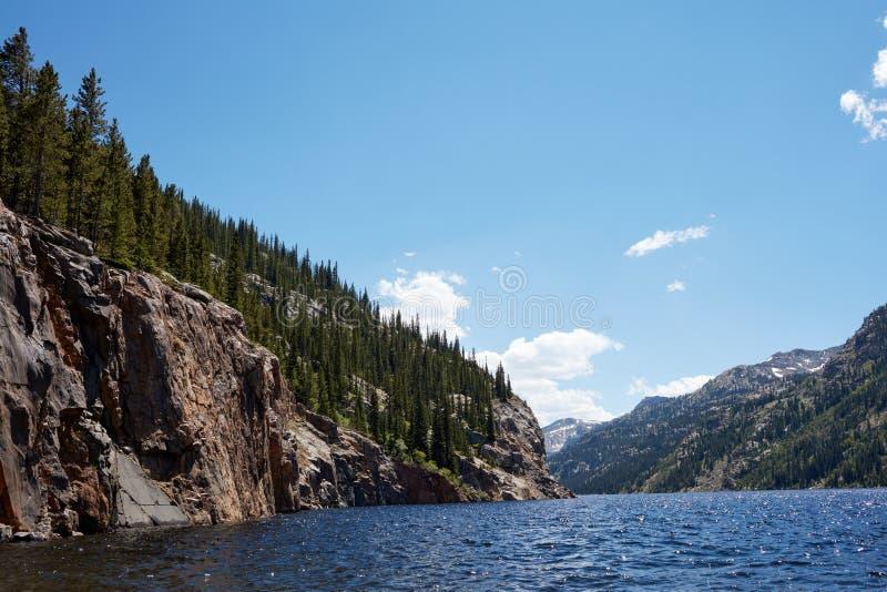 Bosque con los acantilados por el lago de la montaña foto de archivo