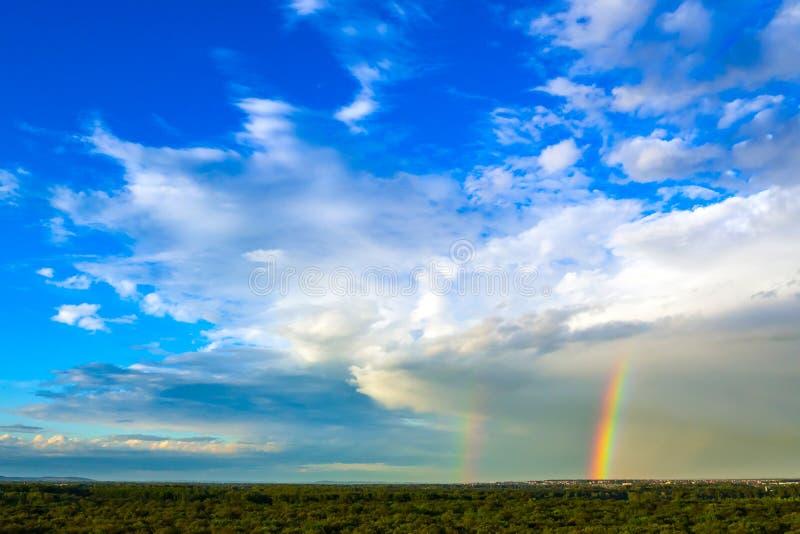 Bosque del verde del paisaje, cielo azul con las nubes blancas y arco iris doble fotos de archivo libres de regalías
