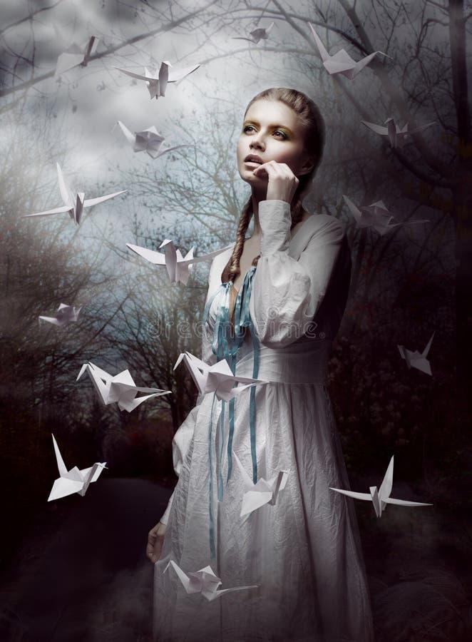 Noche. La mujer en bosque misterioso que lanza el papel hecho a mano Cranes. Origami fotografía de archivo