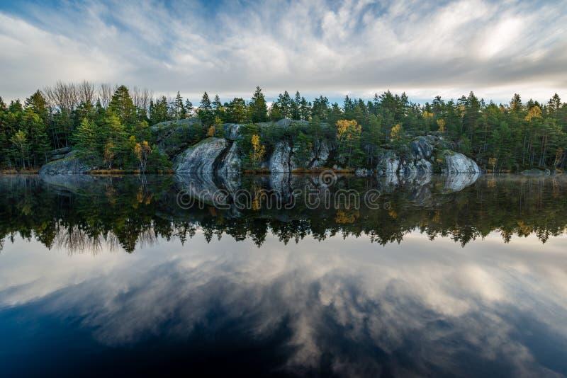 Bosque y acantilados duplicados en el lago tranquilo foto de archivo libre de regalías