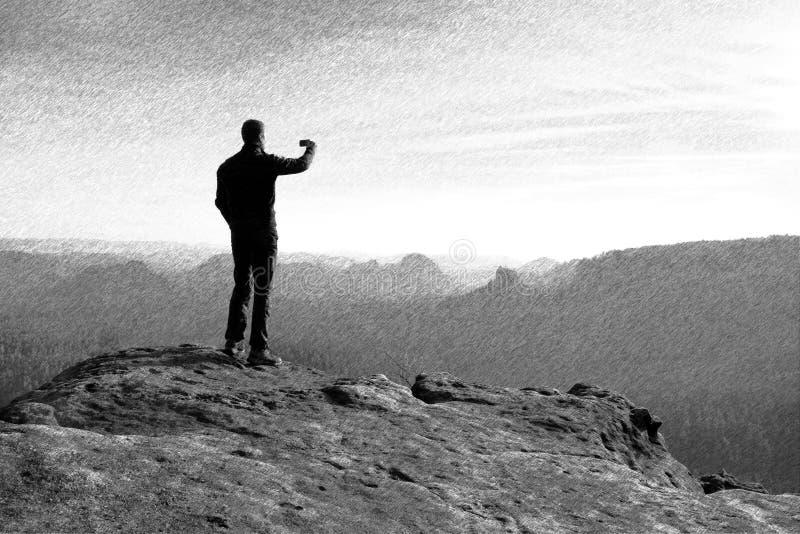 Bosquejo retro rayado blanco y negro El caminante está tomando la foto por el teléfono elegante en el pico de la roca fotos de archivo libres de regalías