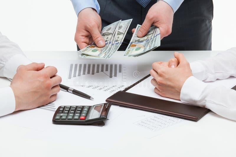 Boss allocating money among collaborators. White background stock photo