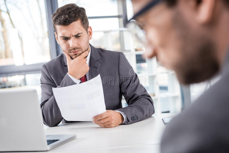 Boss analyzing documents with colleague near by at business meeting royalty free stock image