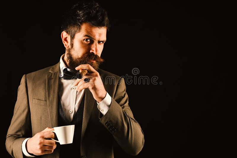 Boss with beard smokes cigar with cup of coffee. Boss with beard smokes cigar with a cup of coffee on black background stock photos