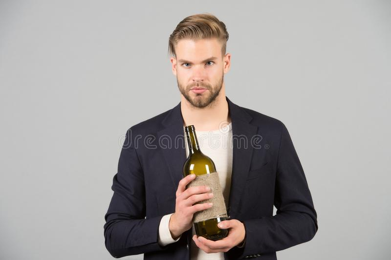Boss with bottle of wine in hands. Bearded man hold alcoholic drink. Sommelier or degustator with wine. Alcohol addiction and bad royalty free stock image