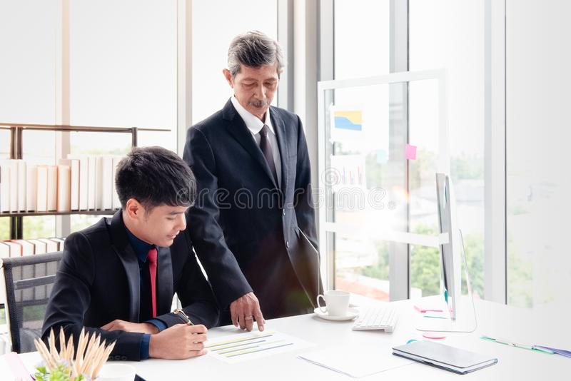 Boss businessman discussing with staff report. The boss businessman stood and checking the point to the report. He is discussing with the young staff on the desk royalty free stock photography