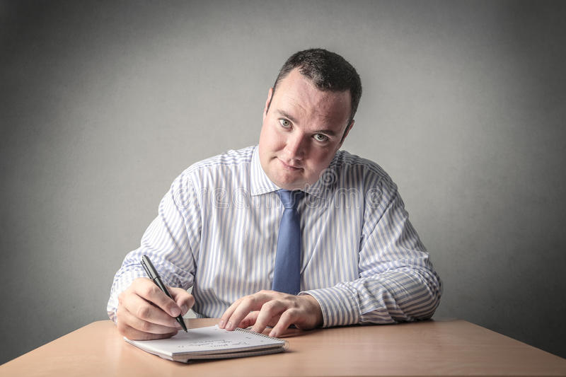 The Boss. A businessman is holding a pen to write something down on a notebook royalty free stock photo