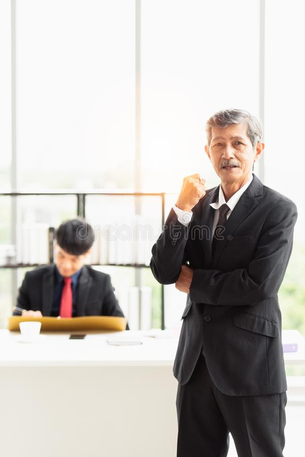 The boss was proud to have an excellent staff. The boss businessman stood and smiled in front. He is proud to have an excellent staff member working in the royalty free stock photography