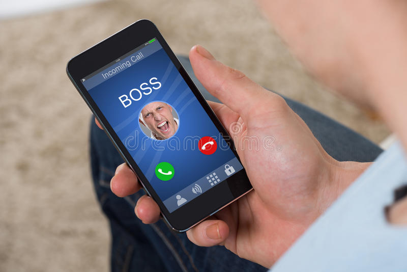 Boss Calling On Mobilephone. Person Hand Holding Mobile Phone With Angry Businessman Boss Calling stock photo