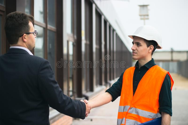 Boss or Chief handshaking with workers engineers and giving salary in an envelope. Business modern background. royalty free stock photography