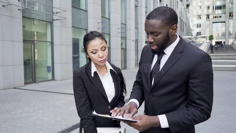 Boss commenting on files to personal assistant near office, important documents stock images