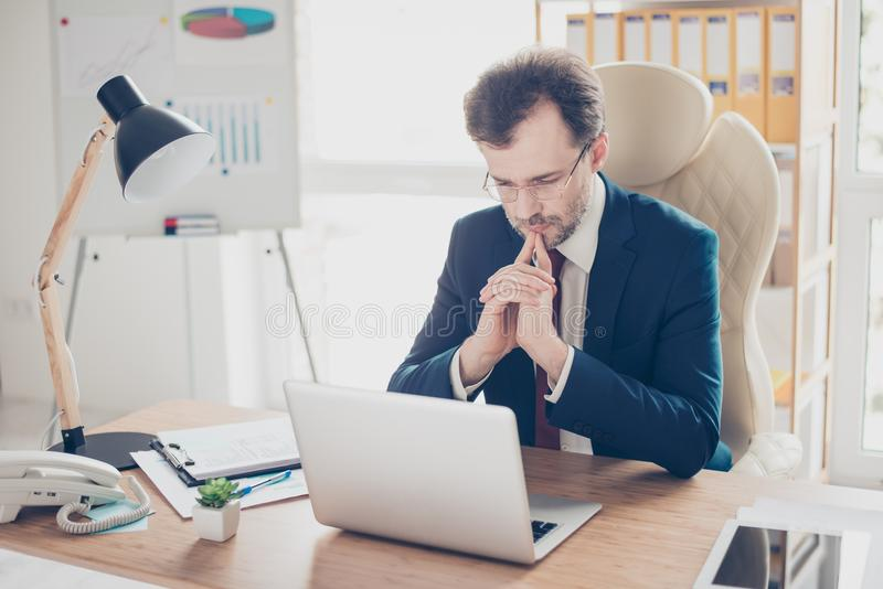 Boss is concentrated on decisionmaking, he has a lot of options, but need to make right choice. He is wearing formalwear, glasses. Sitting in modern office royalty free stock image