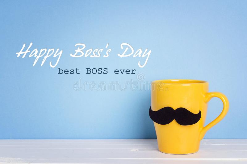 Boss day background with yellow mug with a mustache on blue. Happy boss day concept royalty free stock photo