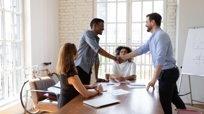 Boss, der eine Vereinbarung mit dem Kunden trifft oder Lob für Mitarbeiter im Büro stockfotografie