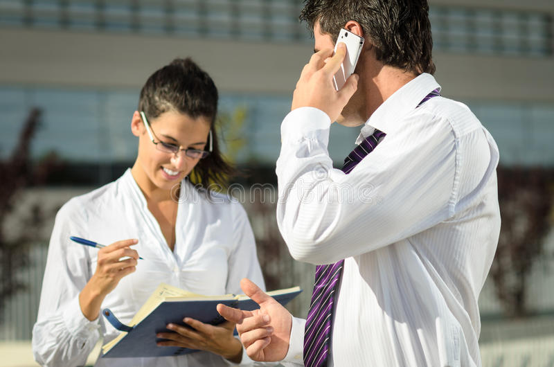 Boss dictating notes. To his cheerful assistant while talking by phone stock images