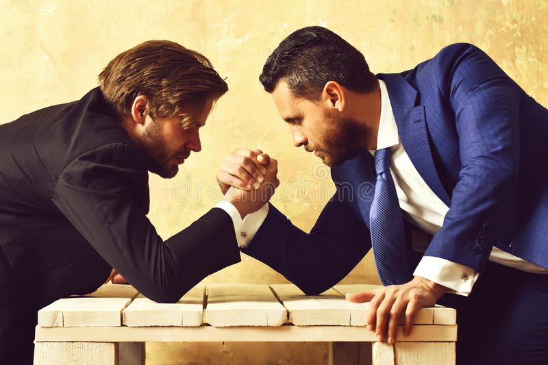 Boss and employee arm wrestling in office. Boss and employee compete in arm wrestling in office. Superior concept stock photo