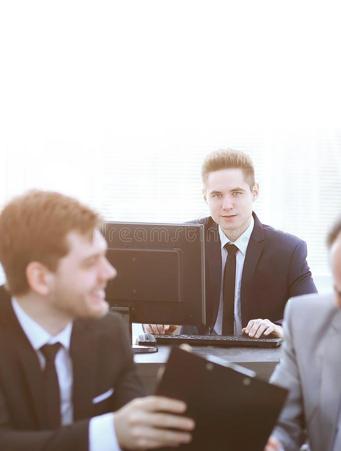 Boss and employee discussing the document sitting at the Desk in the office. Photo with copy space royalty free stock image