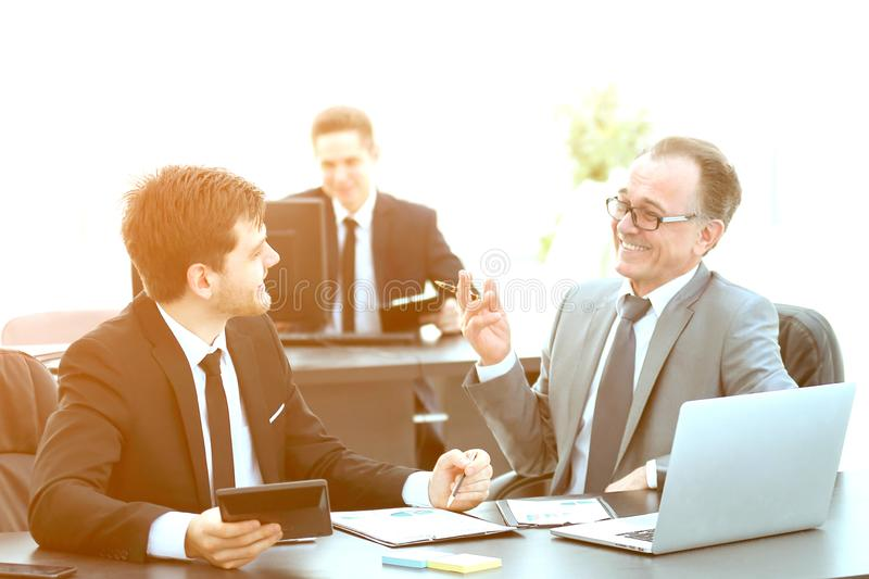 Boss and employee discussing the document sitting at the Desk in the office. Photo with copy space royalty free stock photography