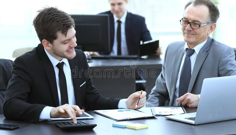 Boss and employee discussing the document sitting at the Desk in the office. Photo with copy space royalty free stock photos
