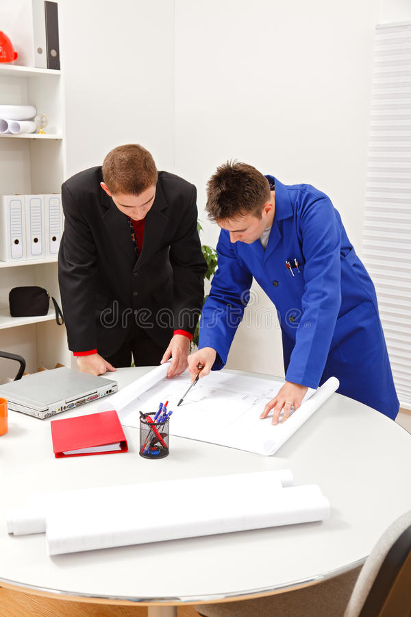Boss and employee surveying plans stock photos